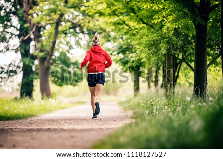 Running woman, enjoying summer day in park. Endurance training, jogging or power walking female athlete, physical activity concept outdoors. #1118127527