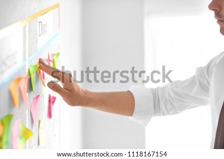 Man attaching sticky note to scrum task board in office #1118167154