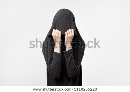 Woman hiding face under the clothes. She is oulling sweatr on her head. Depressed emotion. Wish to ba alone. Protection of personal space Royalty-Free Stock Photo #1118255228