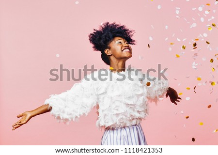 A magical time - Portrait of a very happy girl with arms out, smiling at confetti falling	 #1118421353