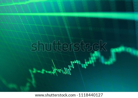 Analysing stock market data on a monitor. Investing and concept gain and profits with faded candlestick charts. Finance concept.  Professional market analysis. Market report on blue background.