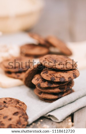 Stack of chocolate cookies biscuits on a napkin with rustic wooden table background. vintage look #1118612720
