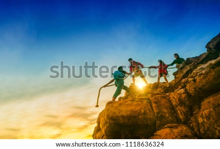 Young asian couple climbing up on the mountain,hiking and team work concept, Sunset background.