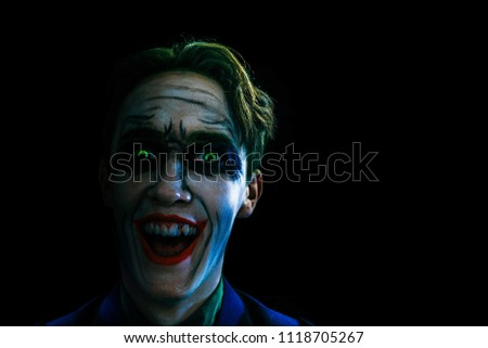 Bloody Halloween theme. The crazy joker face on black background. Comics heroes. Copy space for text.