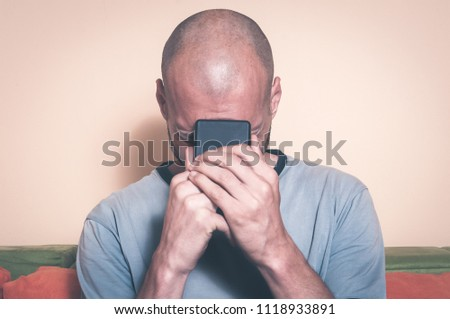 Sad man holding his cell phone in his hands and cry because his girlfriend break up with him over the text message #1118933891