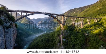 Beautiful misty morning view of Djurdjevica bridge over the river Tara in Montenegro, Europe. Beautiful world of Mediterranean countries. Aerial panorama. #1118941712