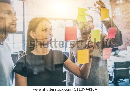 Business people meeting at office and use post it notes to share idea. Brainstorming concept. Sticky note on glass wall. Royalty-Free Stock Photo #1118944184
