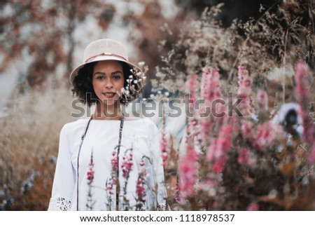 Portrait of a young happy black tourist female in the hat and chemise standing on the summer field, surrounded by colorful native grasses and flowers and looking at the camera; shallow depth of field