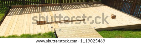 New constructed garden wooden decking laid over a garden incline.