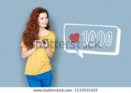 Popular blogger. Cheerful popular blogger looking glad while standing with a smartphone and checking the number of followers Royalty-Free Stock Photo #1119035429