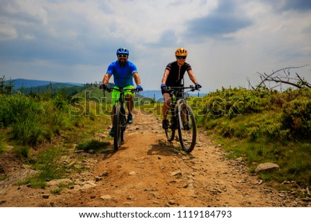 Cycling woman and man at Beskidy mountains forest landscape. Couple riding MTB enduro track. Outdoor sport activity. #1119184793