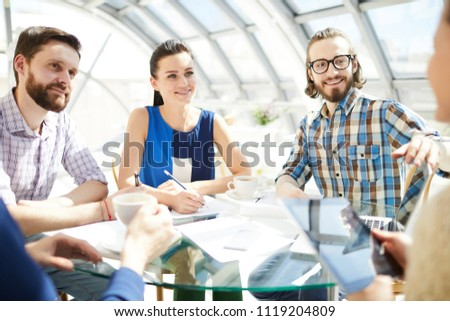 Three young employees looking at colleague and listening to her explanations of working points at start-up meeting #1119204809