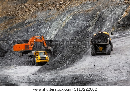 Excavator in an open coal mine. Heavy industry. Two quarry dump trucks. #1119222002