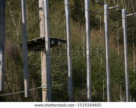 Detail of a wooden platform and wooden hanging obstacles in a circuit at an outdoor adventure park with green forest on the background #1119264605