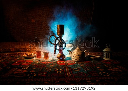 Hookah hot coals on shisha bowl making clouds of steam at Arabian interior. Oriental ornament on the carpet eastern tea ceremony. Stylish oriental shisha in dark with backlight. Selective focus #1119293192