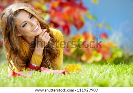 beautiful girl with book in the autumn park #111929909