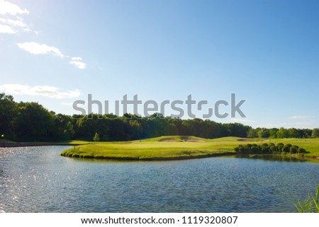 Picture of a green golf course from across the lake. Forest in the background. Beautiful still water, blue sky with a couple of clouds.