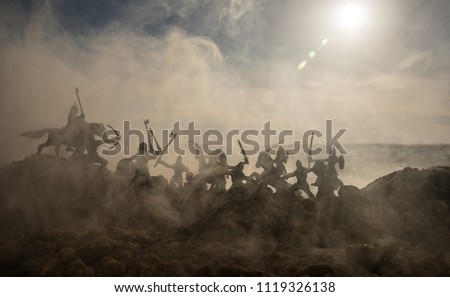 Medieval battle scene with cavalry and infantry. Silhouettes of figures as separate objects, fight between warriors on sunset foggy background. Selective focus #1119326138