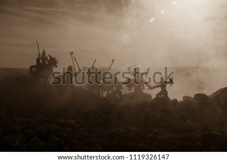 Medieval battle scene with cavalry and infantry. Silhouettes of figures as separate objects, fight between warriors on sunset foggy background. Selective focus #1119326147