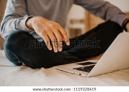 Working moments at home.Young caucasian coworker man in casual clothes working on laptop at modern apartment. Blurred background #1119328619