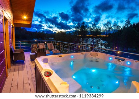 View from the house to the pool. Hydromassage. Pool on the balcony of the cottage. Jacuzzi on the background of the evening sky. Cottage with spa complex. House with pool. #1119384299
