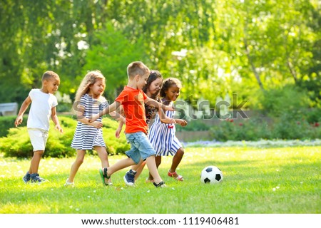 Cute little children playing football outdoors Royalty-Free Stock Photo #1119406481