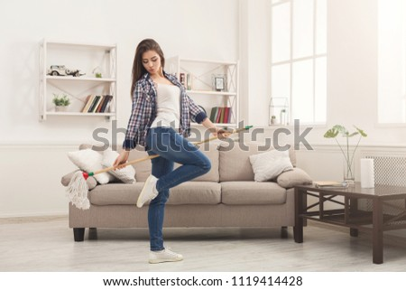 Happy woman cleaning home, dancing with mop and having fun, copy space. Housework, chores concept #1119414428