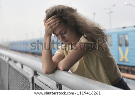Depressed young woman at railway station #1119416261