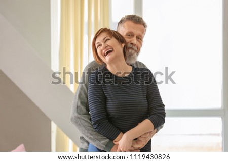 Happy mature couple hugging at home #1119430826
