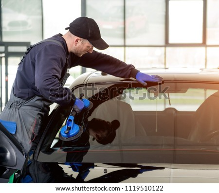 Automobile special workers replacing windscreen or windshield of a car in auto service station garage. Background Royalty-Free Stock Photo #1119510122