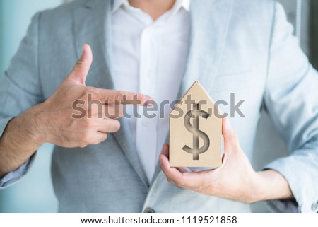 businessman hold house model and point to money sign symbol on house paper model business ideas concept #1119521858