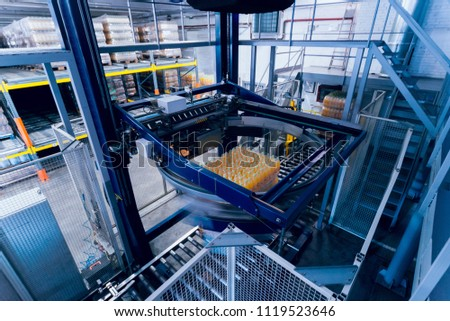 Strapping machine for packaging line. Modern machine for packaging line in factory. Technology and industrial concept. Background #1119523646