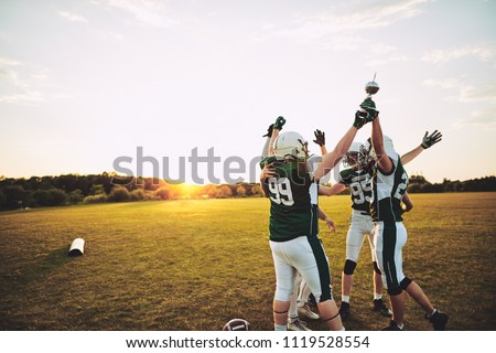Excited group of American football players standing together in a huddle and raising a championship trophy in celebration #1119528554