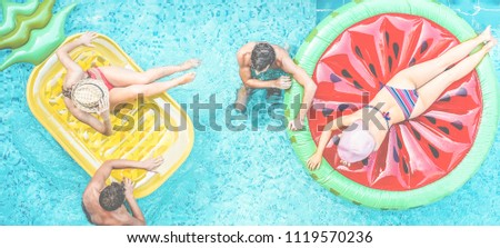 Happy millennials friends having fun floating in swimming pool - Young people enjoying summer vacation in tropical hotel resort - Travel, holidays, youth lifestyle and friendship concept #1119570236