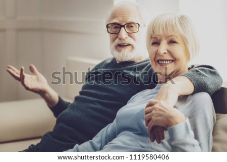 Wonderful mood. Happy delighted woman smiling while sitting on the sofa together with her husband #1119580406