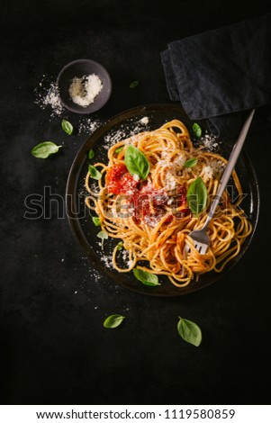 Tasty appetizing classic italian spaghetti pasta with tomato sauce, cheese parmesan and basil on plate on dark table. View from above, top view #1119580859