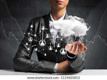 Businessman in suit keeping cloud with network connections in hand with business sketches on background. #1119605813