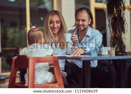 Family and people concept - happy mother, father and the little girl in outdoor cafe. #1119608639