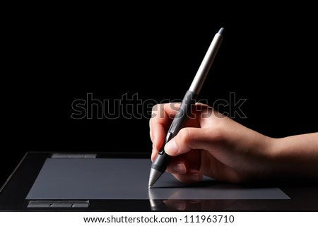 Hand of the designer with a pen on a tablet