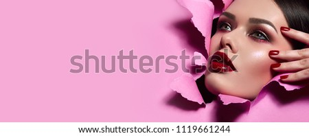the face of a young beautiful girl with a bright make-up and with plump red lips peeks into a hole in pink paper.fashion, beauty, makeup, cosmetics, beauty salon, style, personal care, posture, hair,