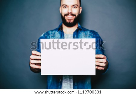 Young man with white blank board in hands isolated on gray. #1119700331