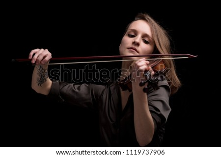 serious and concentrated violin player - portrait of a woman on black background playing strings #1119737906