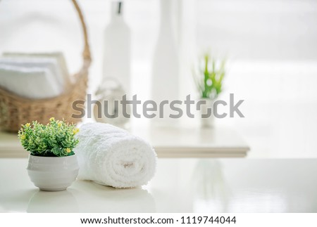 Roll up of white towels on white table with copy space on blurred living room background. For product display montage. #1119744044