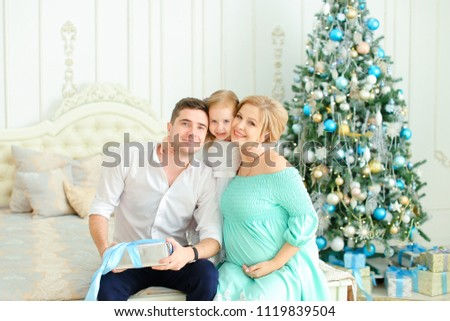 Little caucasian daughter sitting with happy father and pregnant mother on bed near decorated Christmas tree. Concept of european family celebrating winter holidays.