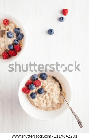 A bowl of oatmeal porridge with blueberries and raspberries on white wooden table. Top view. #1119842291