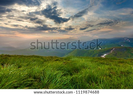 Wide summer mountain view at sunrise. Glowing orange sun raising in blue cloudy sky over green grassy hill soft grass and distant mountain range covered with morning mist. Beauty of nature concept. Royalty-Free Stock Photo #1119874688