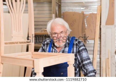 Serious furniture designer carefully polishes the chair frame, which he is busy manufacturing in his woodwork workshop, with shelves of wooden objects and patterns behind him #1119882710