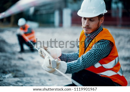 Worker in orange uniform and white helmet. Safety during roadworks Royalty-Free Stock Photo #1119901967