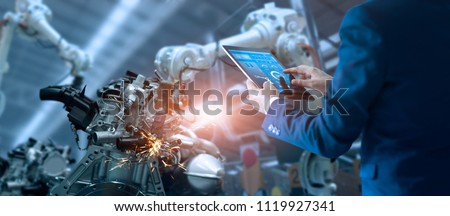 Manager engineer check and control automation robot arms machine in intelligent factory industrial on real time monitoring system software. Welding robotics and digital manufacturing operation.  Royalty-Free Stock Photo #1119927341