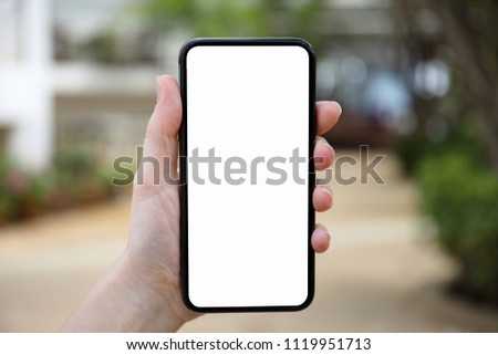 female hand holding phone with an isolated screen on nature background #1119951713